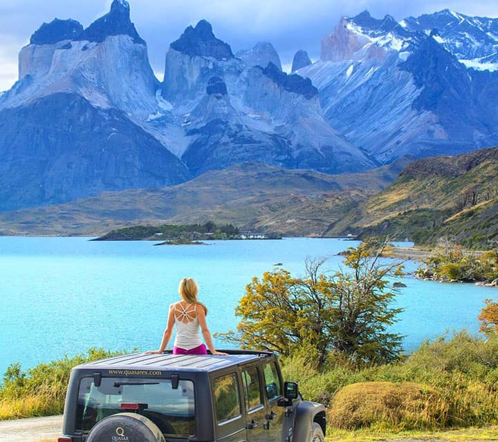 Traveler sitting atop a Quasar Jeep looking out to Torres del Paine National Park