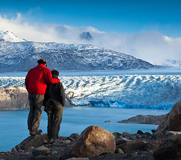 Couple standing on cliffside to view glacier field