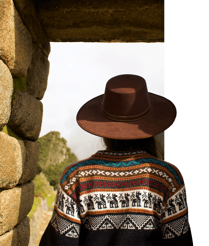 A woman walking thru one of the structures of Machu Picchu