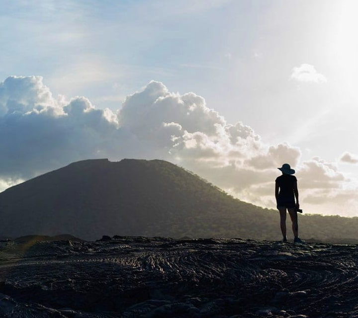Hiker observing the lava fields on a trip to the Galapagos