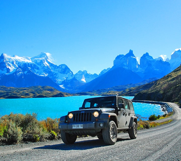 Jeep driving by Lake Pehoe in Torres del Paine National Park