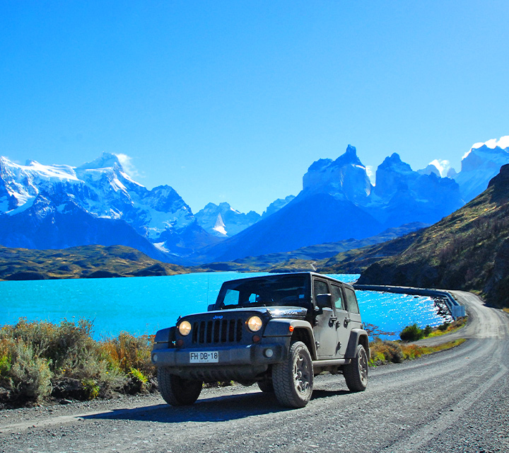 Jeep driving by crystabl blue lagoon in Torres del Paine National Park, Chile