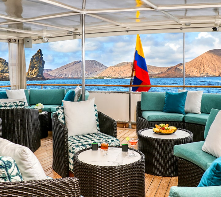Covered outdoor deck on Grace Yacht with Kicker Rock in Bartolome Island, Galapagos in the background