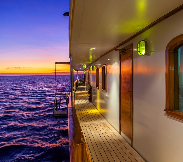 Spacious exterior of Grace Yacht from the side at the golden hour in the Galapagos Islands