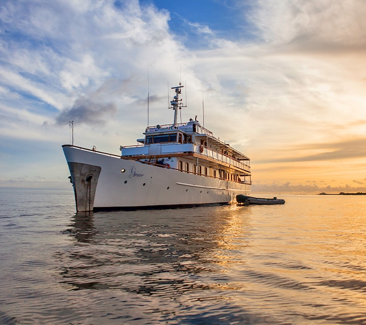 Grace Yacht anchored at sunrise with dinghy, ready to start a new day of exploration in the Galapagos Islands