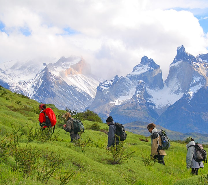 A small group of travelers going uphill in the rolling Patagonian pampas with a dramatic backdrop of Torres del Paine National Park