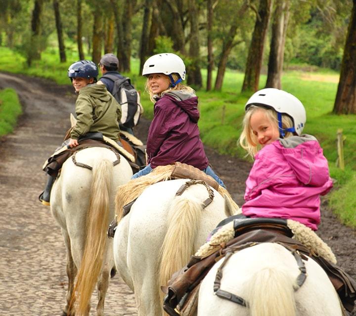 Kids wearing helmets on a guided horseback ride through a national park in Patagonia