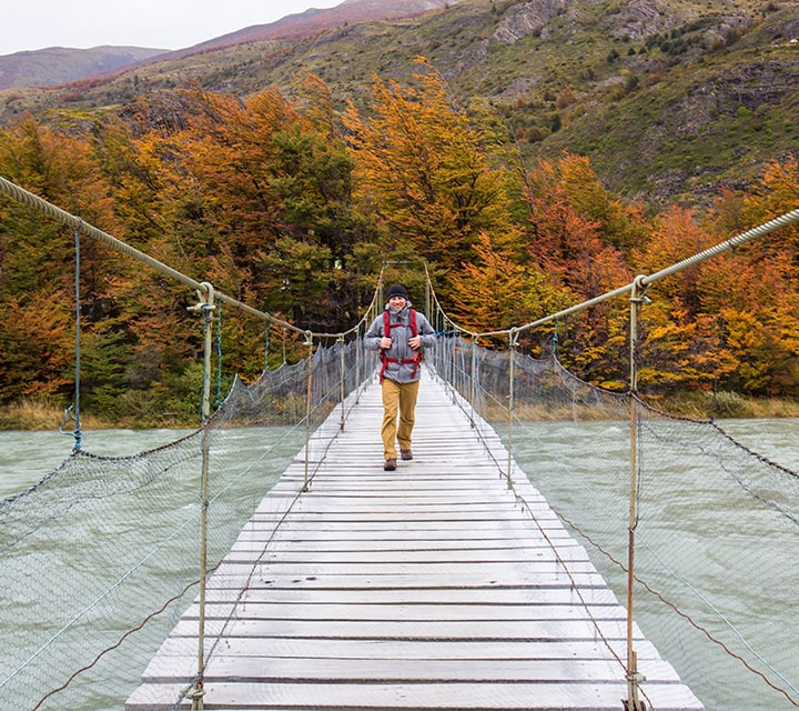 Solo traveler crossing a Patagonian bridge on a day trip to a national park