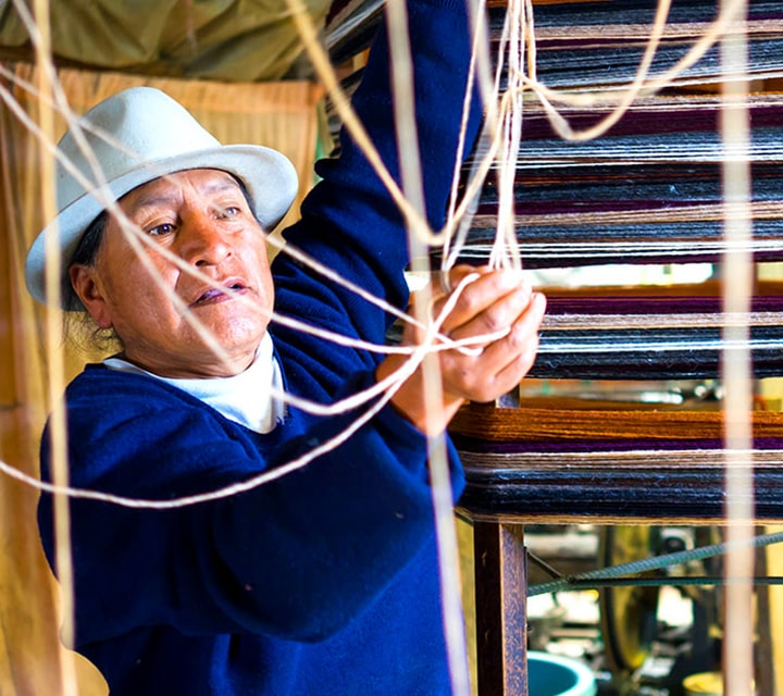 An indigenous Ecuadorian woman weaving fabric into merchandise, a pass down tradition of their ancestors