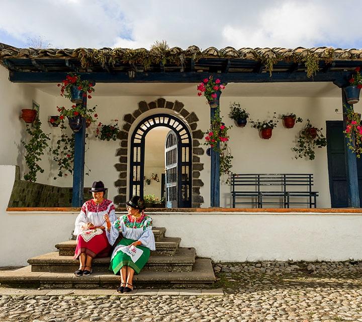 Ecudorian women sitting infront of the colonial-era working farm turned boutique hotel, Hacienda Zuleta in Ecuador