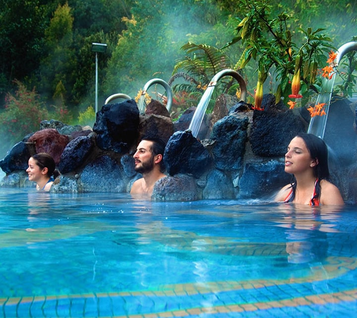 Two women and a man enjoying a soak in the thermal pools of Ecuador's Papallacta Hot Springs and Spa
