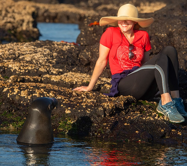 Woman wearing a sun hat sitting on the rocky shore next to a Galapagos Sea Lion