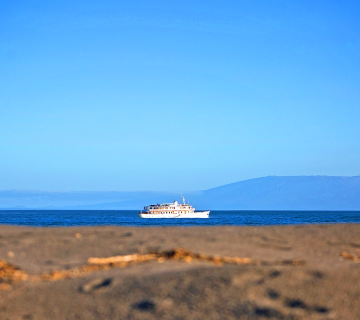 Clear blue skies, view of Grace yacht from land on Galapagos Islands