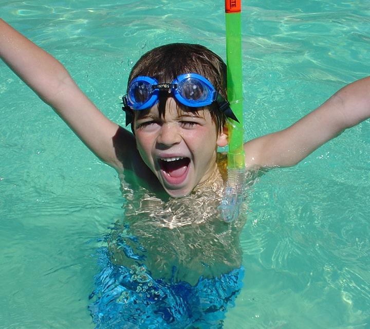 Ecstatic boy in warm Galapagos ocean water