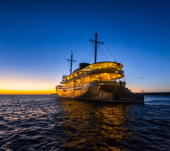 The stern of the Evolution Yacht shown lit up in the Pacific Ocean, Galapagos Islands,Ecuador