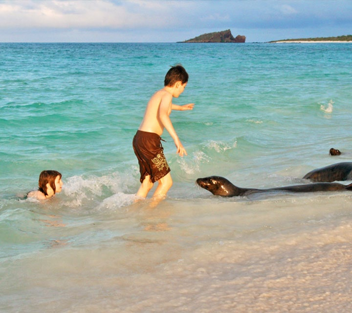 Two kids playing in the water alongside a sea lion in the Galapagos
