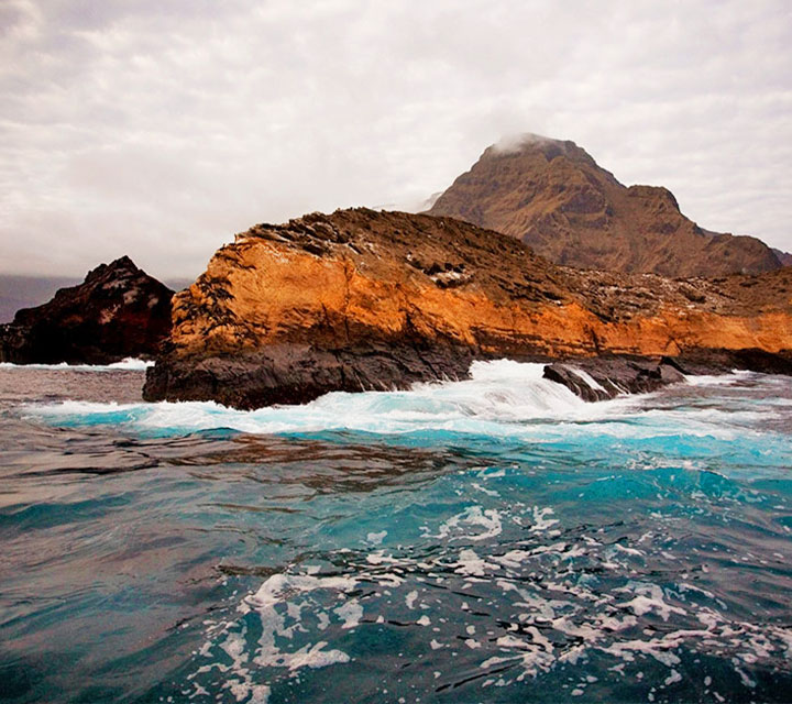 Waves crash on an island in the Galapagos during a rainy day
