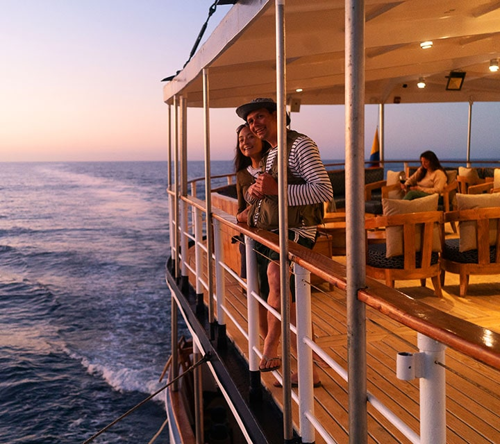 A couple leaning on the rail of the Evolution yacht looking at ocean from the A-deck