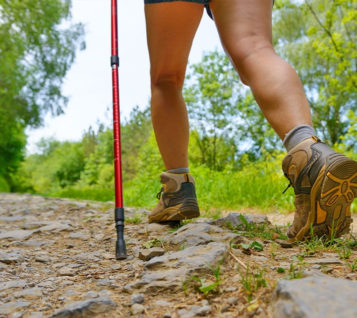 A woman walking with sturdy hiking boots and hiking stick in the Galapagos