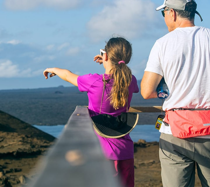 Young girl pointing out to islands from atop Bartolome summit in the Galapagos with Dad