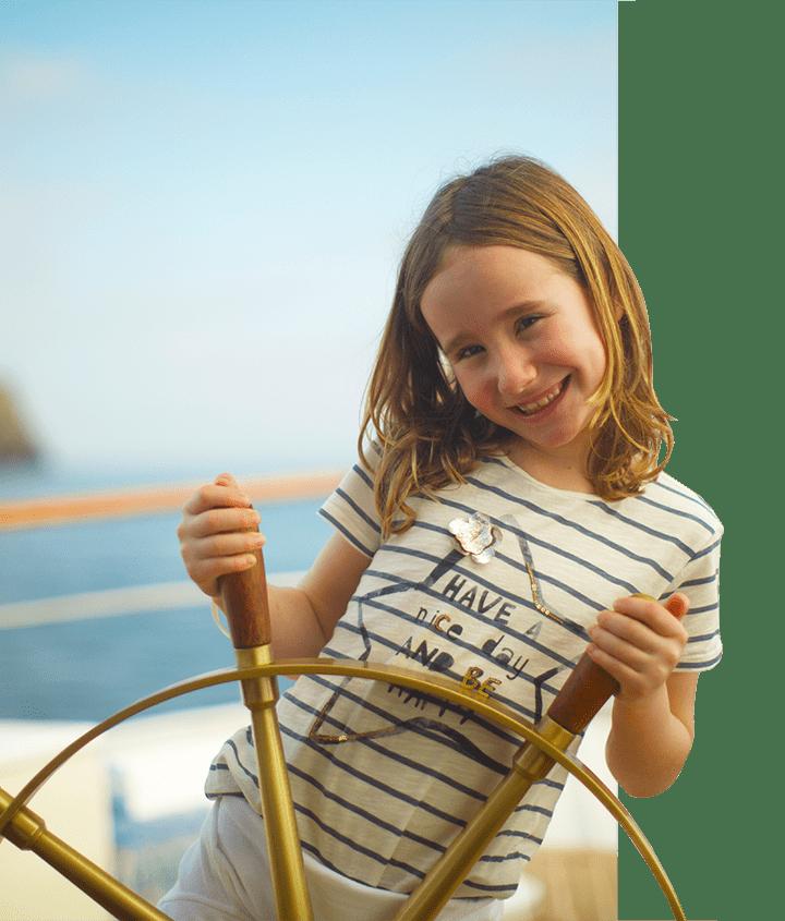 Girl behind ship wheel aboard the Grace Yacht