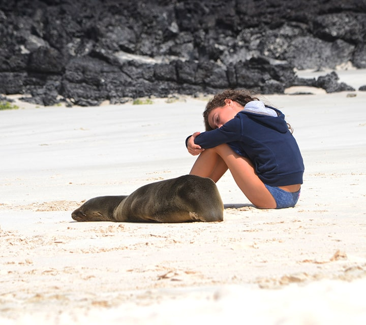 Young girl taking a nap next to a Sea Lion on a white sand beach in the Galapagos